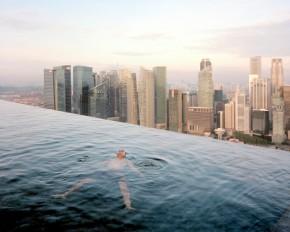 Hombe flotando en la alberca del piso 57 del  Hotel Marina Bay Sands Hotel con la vista del distrito financiero de Singapore  sus espaldas. Paolo Woods & Gabriele Galimberti. 2013